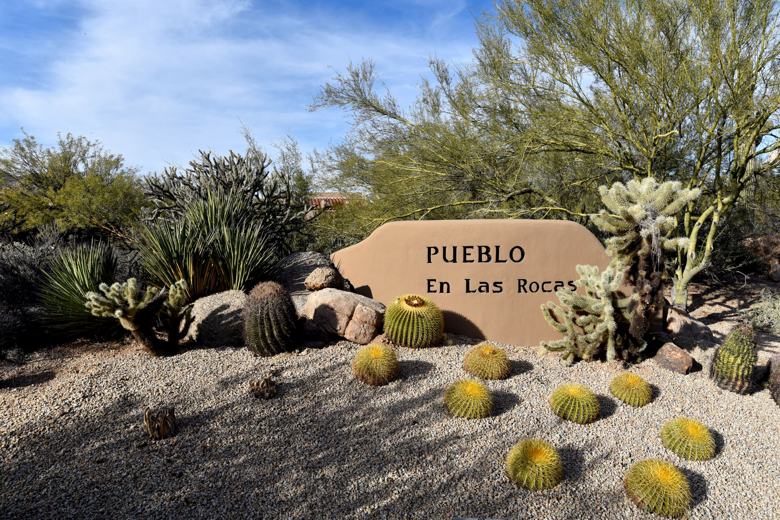 Signage for Pueblos community with cacti and trees